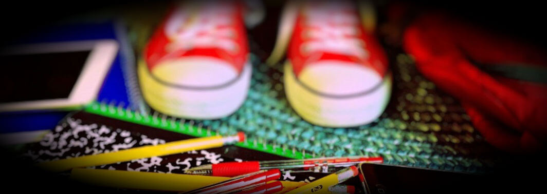 Picture child's feet next to pens, pencils and paper